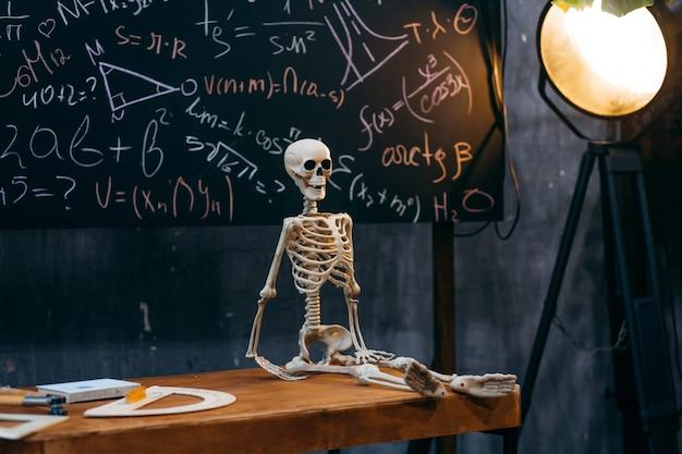 Assis squelette sur le bureau dans la salle de classe