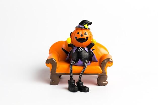 Assistant citrouille halloween assis sur un canapé orange.
