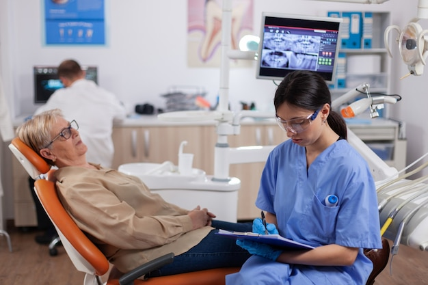Assistant dans le cabinet du dentiste pendant le contrôle d'hygiène bucco-dentaire d'une femme âgée