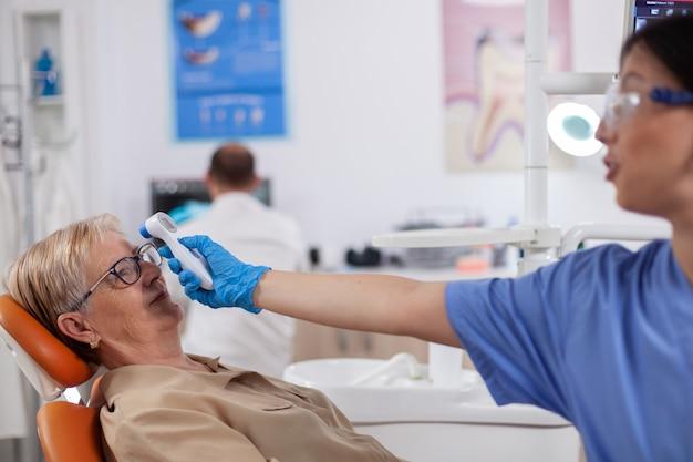 Assistant dentiste tenant un indicateur numérique de température corporelle devant le front du patient assis sur une chaise