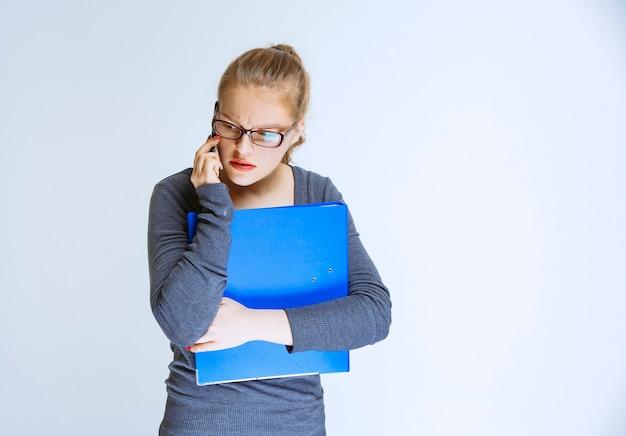 Assistant avec un dossier bleu parlant au téléphone et semble stressé car quelque chose ne va pas.