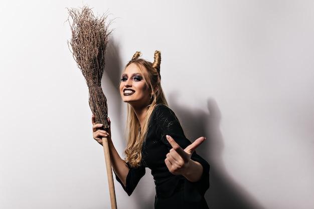 Assistant joyeux au grand chapeau s'amusant à l'halloween. jolie jeune sorcière avec balai dansant avec sourire.
