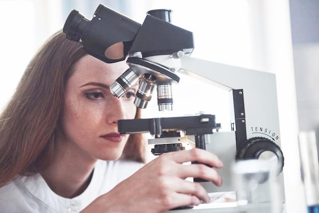 Assistant de laboratoire avec ampoule de verrerie de laboratoire microscope avec des produits chimiques.