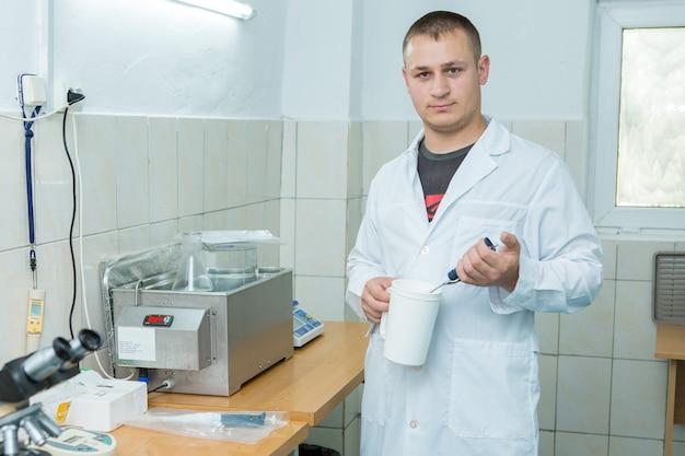 L'assistant de laboratoire en blouse blanche fait des tests au bureau