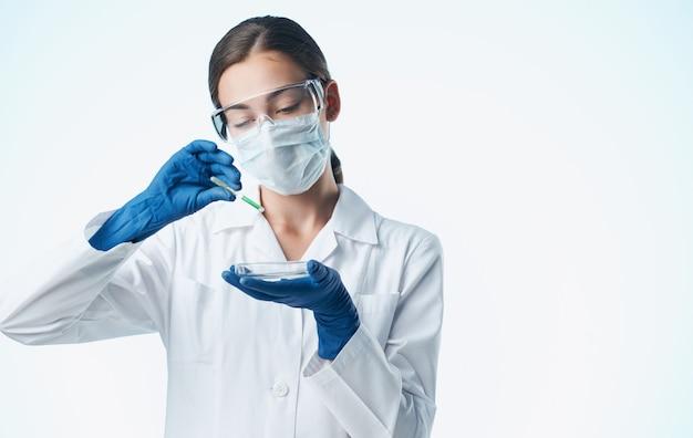 Assistant de laboratoire féminin dans un masque médical avec un élément chimique dans un flacon de vaccination