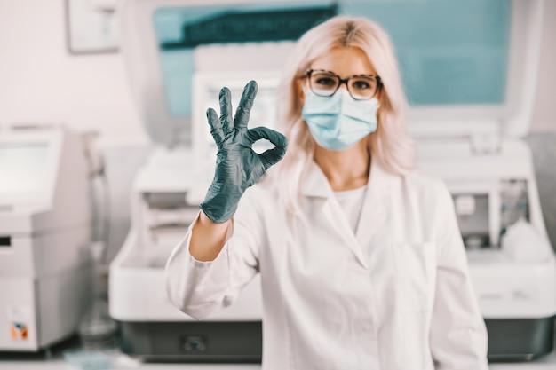 Assistant de laboratoire avec masque facial et gants en caoutchouc debout en laboratoire et montrant le signe correct