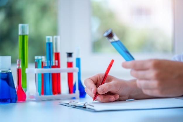 L'assistant de laboratoire mène des recherches cliniques en laboratoire, tient un tube à essai liquide bleu dans ses mains et écrit le résultat de l'étude dans le presse-papiers. concept de médecine, pharmacie et cosmétologie.