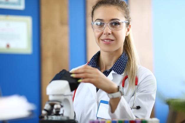 Assistant de laboratoire mener une étude de biomatériau au microscope sur bleu