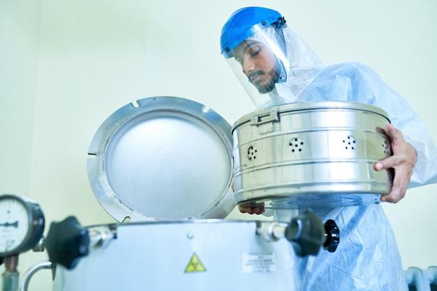 Assistant de laboratoire mettant le récipient dans une centrifugeuse
