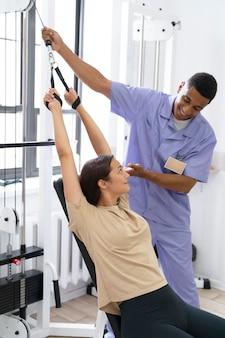 Assistant médical aidant le patient avec des exercices de physiothérapie