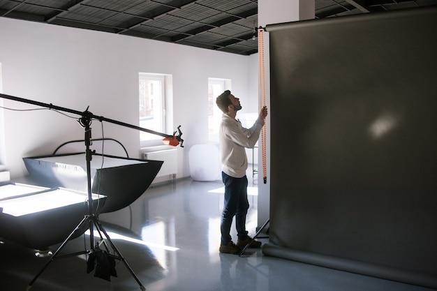 Assistant de mise en place du matériel en studio photo avant la séance photo