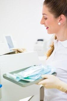 Assistant avec des outils de dentiste stériles