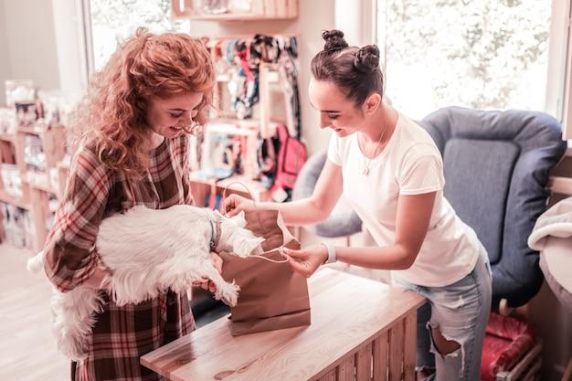 Assistant ouverture sac. agréable assistant commercial souriant du sac d'ouverture de l'animalerie pour chien mignon et moelleux