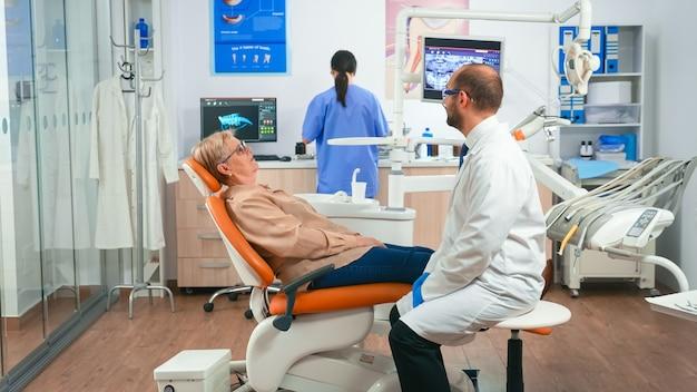 Assistant préparant le patient pour une intervention dentaire mettant un bavoir dentaire pendant que le médecin spécialiste parle avec une femme âgée pointant sur un écran numérique expliquant la radiographie des dents.