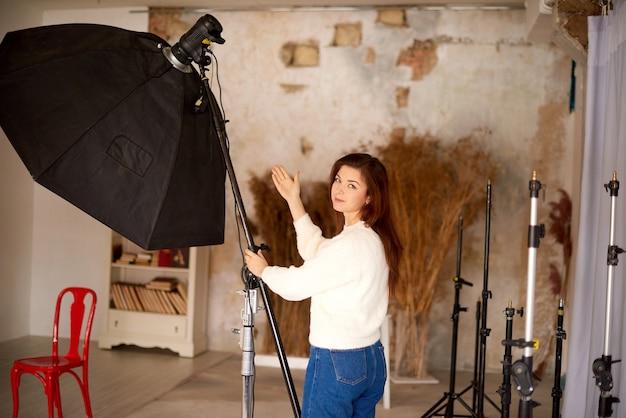 Assistant professionnel en studio photo met en place l'équipement grande softbox photographique