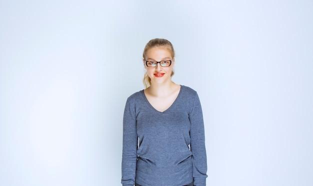 Assistante blonde avec des lunettes souriant et donnant des poses professionnelles.