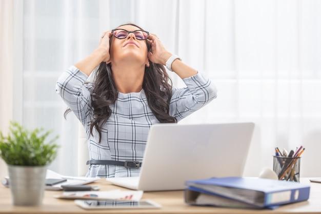 Assistante de bureau se penchant en arrière sur sa chaise avec la tête dans les mains en raison de maux de tête au travail.
