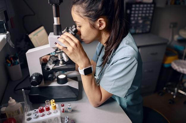 Une assistante de laboratoire asiatique examine le microscope sur le lieu de travail dans le laboratoire de l'hôpital