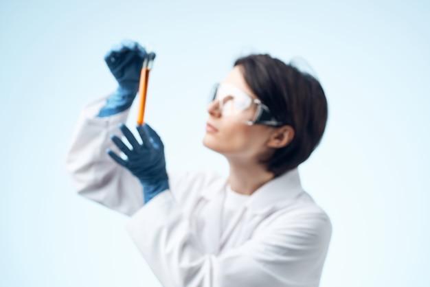 Assistante de laboratoire féminin en blouse blanche solution chimique tube à essai science