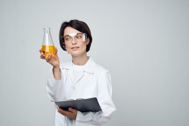 Assistante de laboratoire féminin dans un tube à essai de blouse blanche avec une analyse de solution chimique