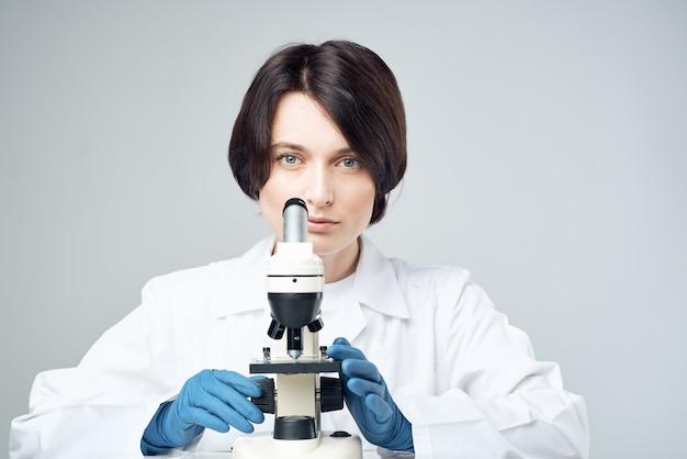 Assistante de laboratoire féminine regardant à travers une science de recherche en diagnostic au microscope. photo de haute qualité