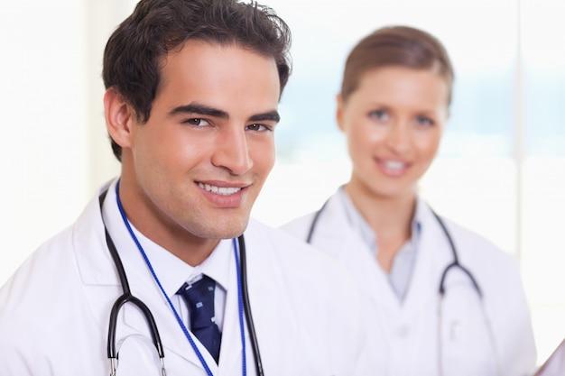 Assistants médicaux souriants debout côte à côte