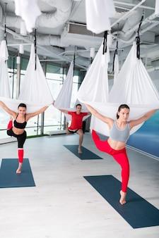 Assister au yoga aérien. les femmes et les hommes actifs se sentent incroyables en assistant à un cours de yoga aérien