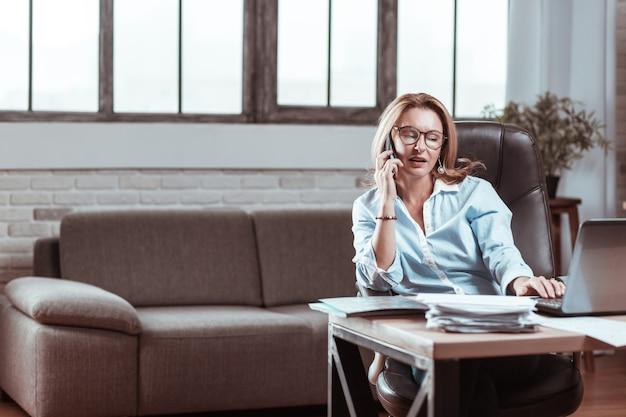 Associé. femme mature séduisante aux cheveux blonds portant des lunettes appelant son partenaire commercial du travail