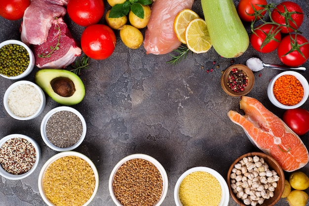 Assortiment d'aliments paléo, y compris légumes, poisson, viande sur fond gris foncé.