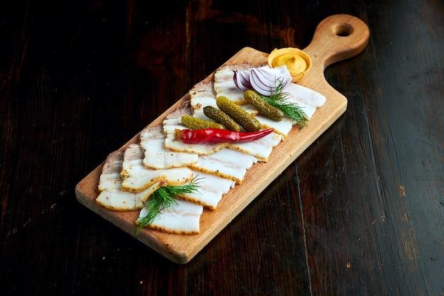 Assortiment de bacon haché ukrainien, salo avec concombre mariné et moutarde, servi sur une planche de bois.