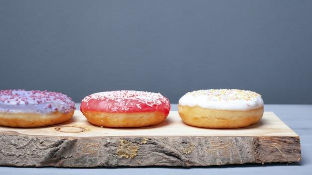 Assortiment de beignets multicolores rouges, blancs, violets enrobés de glaçure et saupoudrés de poudre de pâques sur un support en bois sur un fond gris, des aliments éco sucrés.