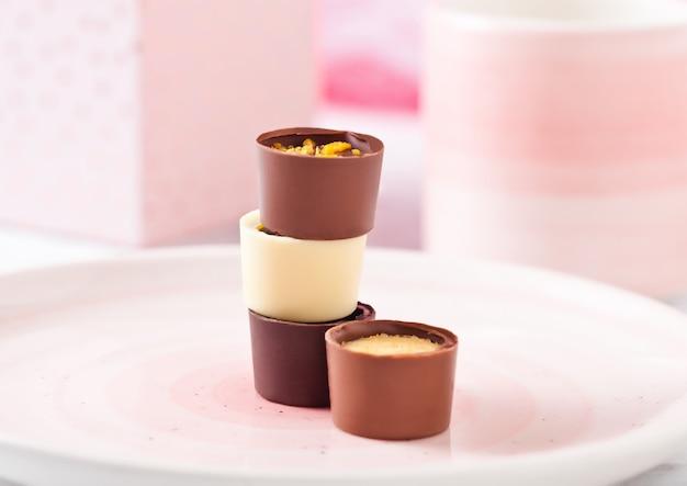 Assortiment de bonbons de luxe au chocolat blanc et noir sur plaque rose avec tasse et boîte-cadeau