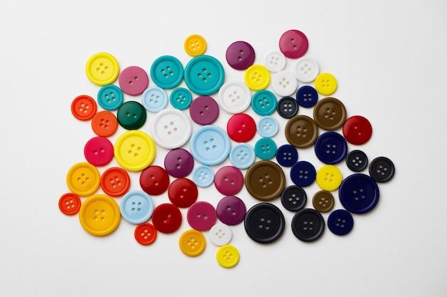 Assortiment de boutons colorés sur surface blanche