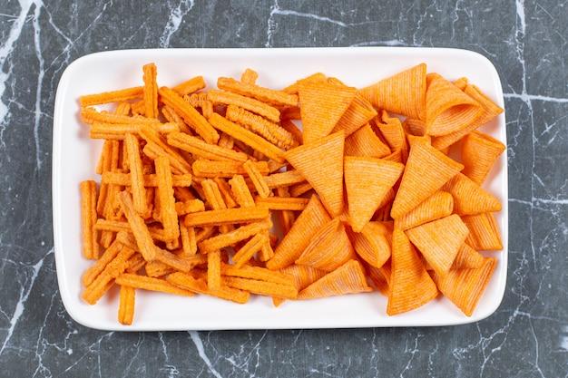Assortiment de chips épicées sur plaque blanche.