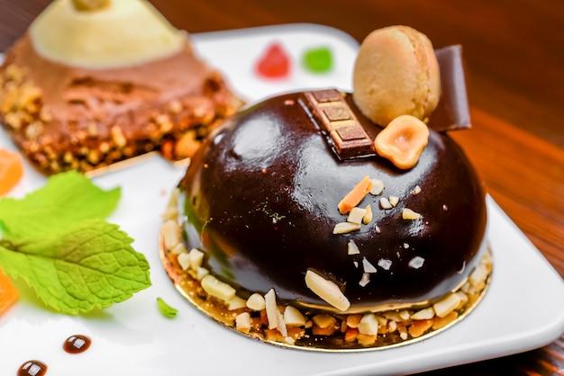 Un assortiment de chocolat blanc, noir et au lait avec des noix, des muffins et des macarons