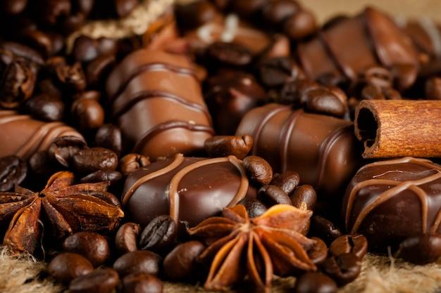 Assortiment de chocolat blanc, noir et lait. chocolat à la crème, noix, amandes, noisettes et cannelle avec grains de café. nourriture sucrée et aucun concept de régime.