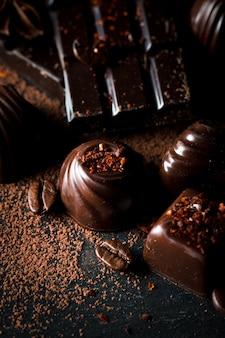 Assortiment de chocolat noir, blanc et au lait sur fond sablant en bois rustique.