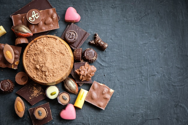 Assortiment de chocolat et de poudre de cacao sur fond noir