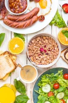 Assortiment de choix de petit-déjeuner. petit-déjeuner anglais, saucisses, œufs au plat, bacon, salade, granola