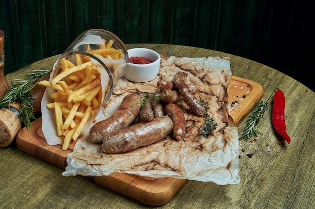 Assortiment de collations à la bière - saucisses frites et frites sur un plateau en bois. vue rapprochée avec copie espace