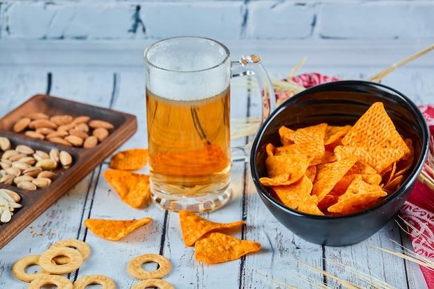 Assortiment de collations, frites et bière sur table bleue. table pour groupe d'amis.