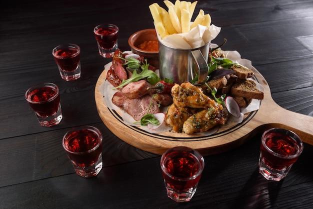 Assortiment de collations de saucisses, ailes de poulet, frites, croûtons, sauce sur une assiette en bois sur une table en bois sombre. de l'alcool rouge en piles autour d'une assiette de collations.