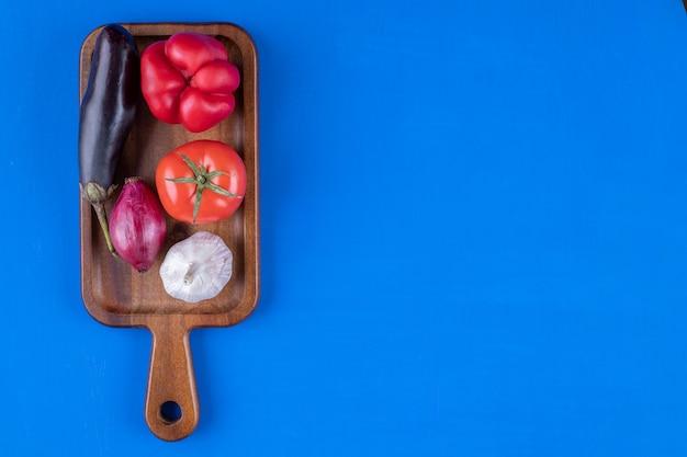 Assortiment coloré de légumes mûrs frais sur planche de bois.