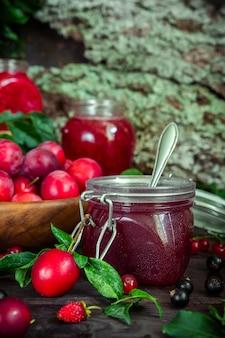 Assortiment de confitures dans des bocaux en verre, des baies fraîches et de la prune aux fruits