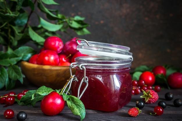 Assortiment de confitures dans des bocaux en verre, baies fraîches de saison et prune aux fruits, fraise, curran
