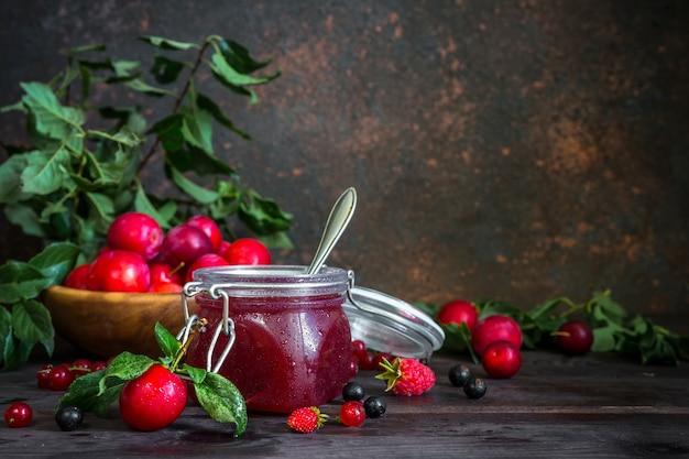 Assortiment de confitures dans des bocaux en verre, baies fraîches de saison et prunes aux fruits
