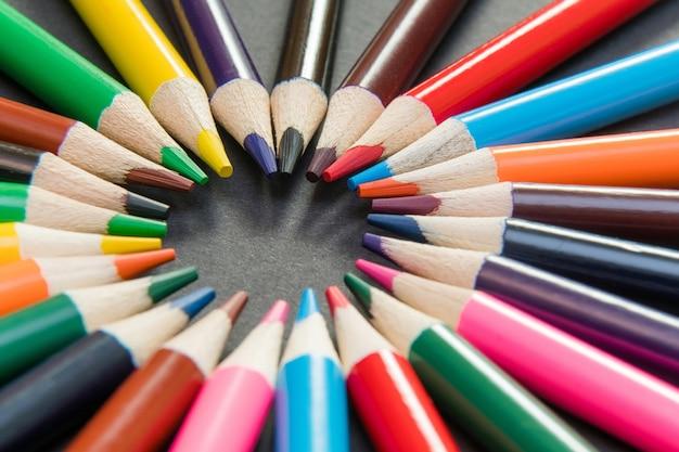 Un assortiment de crayons de couleur en cercle, en spirale sur une surface noire.