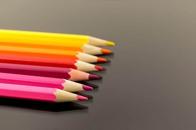 Assortiment de crayons de couleur empilés peu profonds sur un fond noir