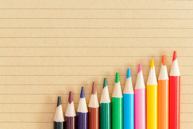 Un assortiment de crayons de couleur sur la surface du cahier.
