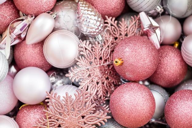 Assortiment de décoration de noël. nouvel an. mélange de boules de neige et de jouets en argent et en or rose